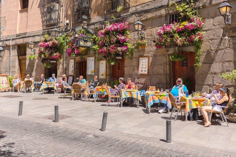 Hemtrevlig gata i Madrid med den lilla restaurangen med utomhus- tabeller i centrum nära plazaen de San Miguel som är full av att royaltyfria bilder