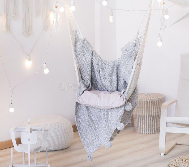 Hemtrevlig hängmattastol i ett ljust rum Ensam fryst tree Grå överkast En girland av ljusa kulor royaltyfri fotografi