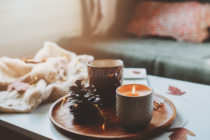 hemtrevlig höst- eller vintermorgon hemma Stillebendetaljer med kopp te, stearinljus, skissar boken med herbariumen och den varma royaltyfria bilder