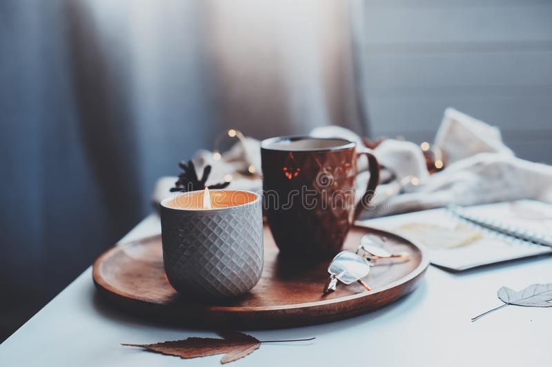 hemtrevlig höst- eller vintermorgon hemma Stillebendetaljer med kopp te, stearinljus, skissar boken med herbariumen och den varma royaltyfri fotografi