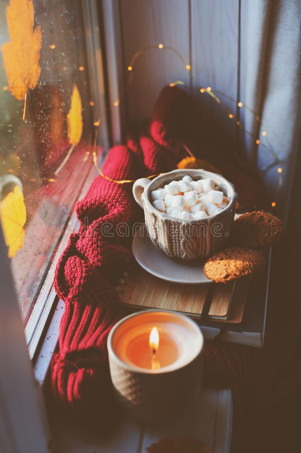 Hemtrevlig höstmorgon hemma Varm kakao med marshmallower och stearinljuset på fönster i regnig kall dag arkivbilder