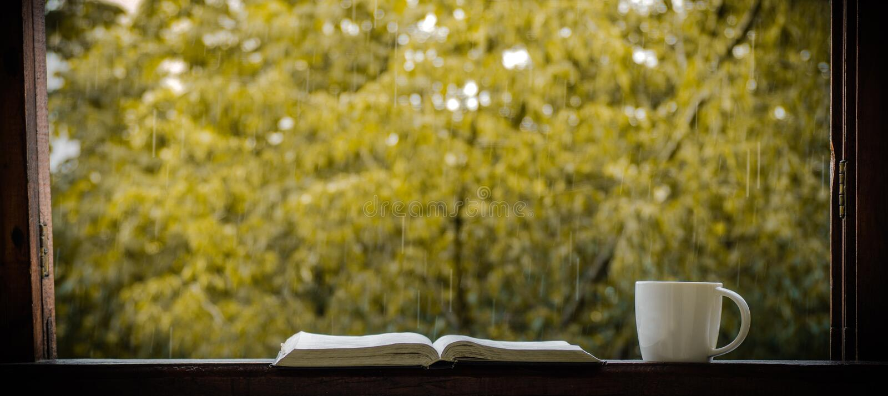 Hemtrevlig höststilleben: kopp av varmt kaffe och den öppnade boken på tappningfönsterbräda och regn utanför Höst _ regn royaltyfria foton