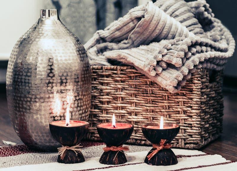 Hemtrevlig hemmiljödekor, brinnande stearinljus på enfärgad filt på bakgrunden av en metallvas royaltyfri bild