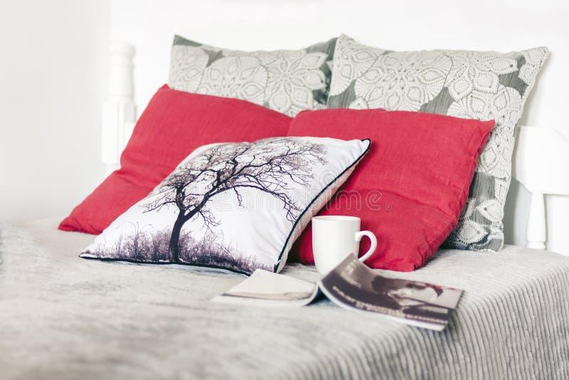 Hemtrevlig hemmiljödekor, vit träsäng med en grå överkast, dekorativa kuddar, en kopp kaffe och en öppen tidskrift arkivfoton