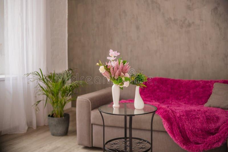 Hemtrevlig hemmilj?vardagsrum med en brun soffa och en vas med blommor och dekorobjekt p? en liten tabell uttrycka med royaltyfria bilder