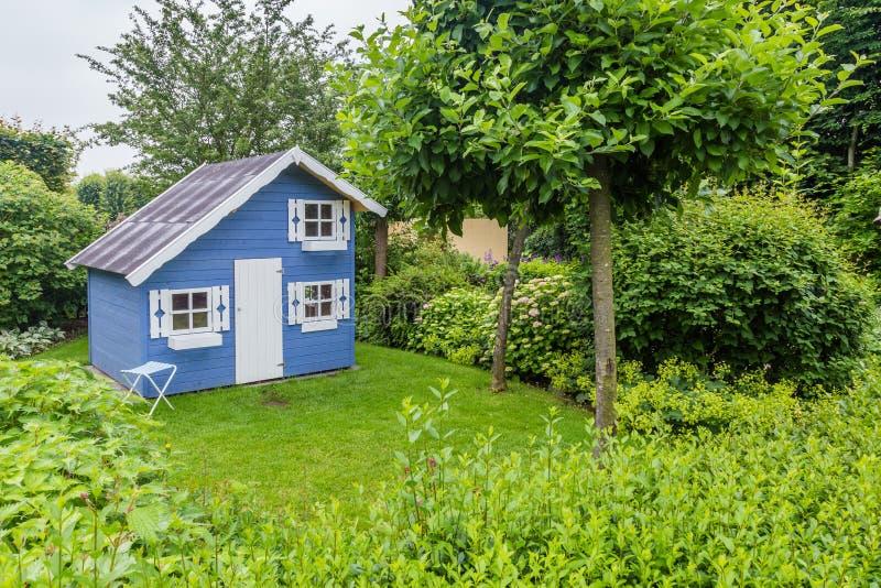 Hemtrevlig liten lekstuga i en grön trädgård arkivfoton