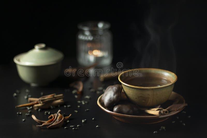 Hemtrevlig mörk stilleben med koppen av varmt te med pepparkakakakan royaltyfri bild