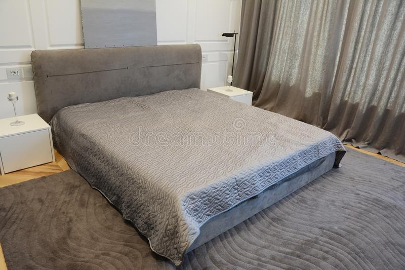 Hemtrevlig modern sovruminredesign med lyxig säng, den moderna lampan och fönstergardiner arkivbild