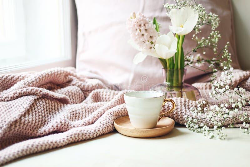 Hemtrevlig påsk, vårstillebenplats Kopp kaffe, rosa stucken pläd och blom- bukett i vas på fönsterbräda royaltyfri fotografi