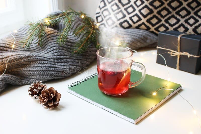Hemtrevlig plats för frukost för julmorgon Ånga exponeringsglaskoppen av varmt fruktteanseende nära fönster på anteckningsboken b royaltyfria foton