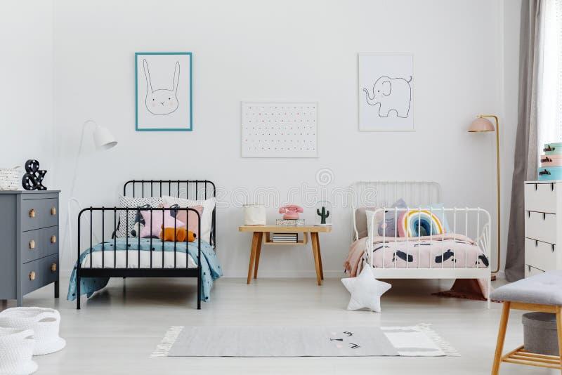 Hemtrevlig sovruminre för syskon Två sängar, en vit, en bla fotografering för bildbyråer
