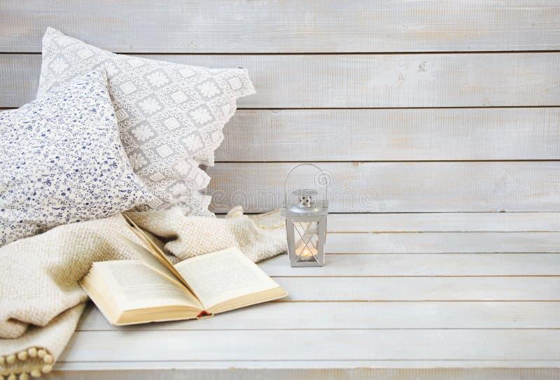 Hemtrevlig stilleben med lyktan, kuddar, boken och plädet royaltyfri fotografi