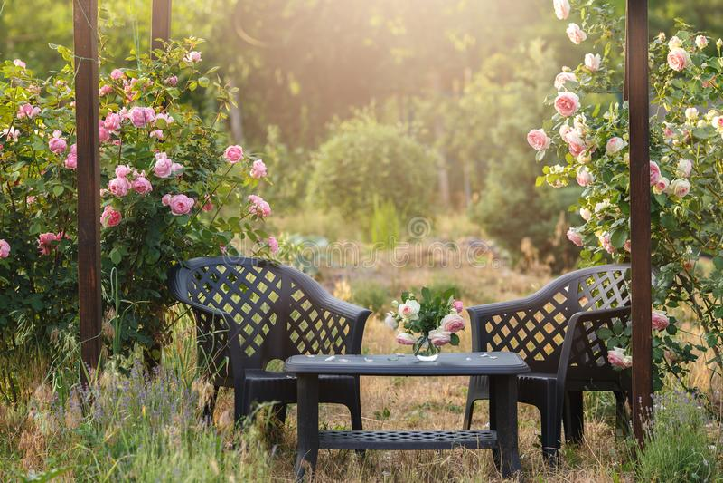 Hemtrevlig trädgårduteplats under en båge av att blomma rosor Bekvämt härligt möblemang för att koppla av royaltyfri bild