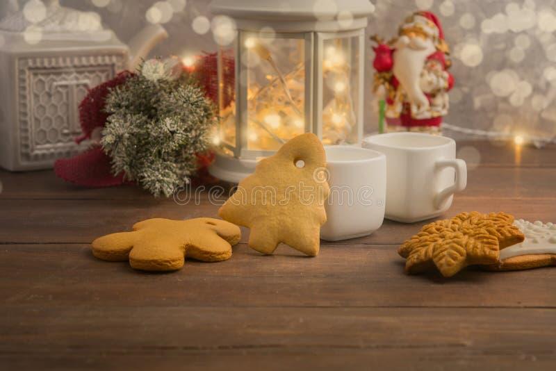 Hemtrevlig vinter hemma med den varma drinken och kakor Jul tajmar med te och girlanden arkivbilder