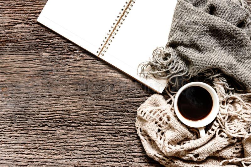 Hemtrevlig vinterbakgrund, koppen av varmt kaffe med marshmallowen och bokanmärkningen, värme den stack tröjan på gammal träbakgr royaltyfri bild