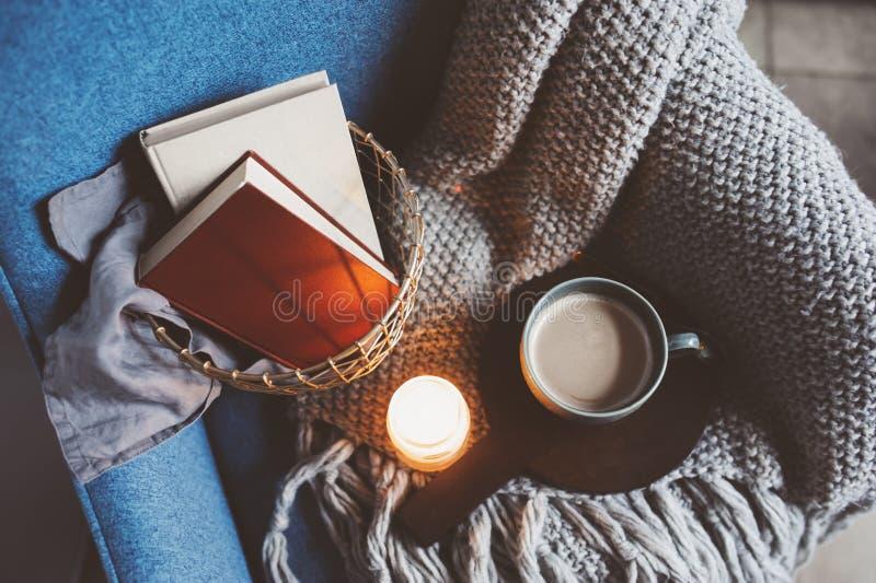 Hemtrevlig vinterhelg hemma Morgon med kaffe eller kakao, böcker, varm stucken filt och nordisk stilstol Hygge begrepp arkivfoto