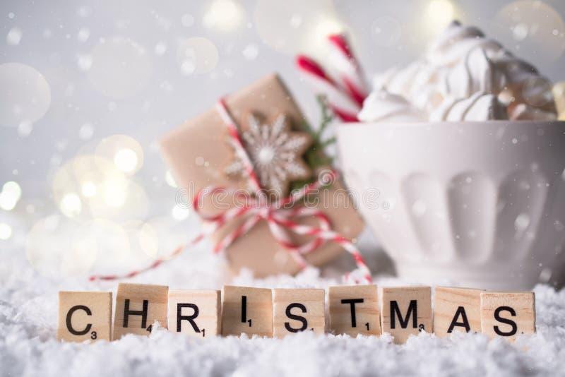 Hemtrevlig vintersammansättning med en kopp av varm choklad med kakor och gåvan för marshmallowpepparkakaman på en festlig bakgru fotografering för bildbyråer