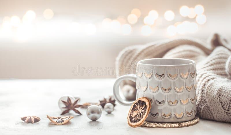 Hemtrevlig vintersammansättning med en kopp och en tröja arkivfoton