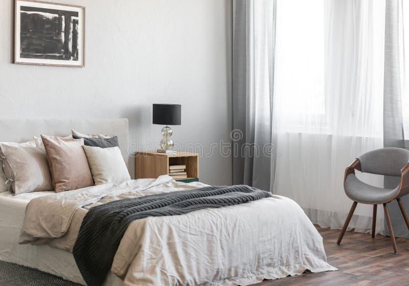 Hemtrevliga kuddar på bekväm stor konungformatsäng i det ljusa sovrummet som är inre i elegant lägenhet arkivbild