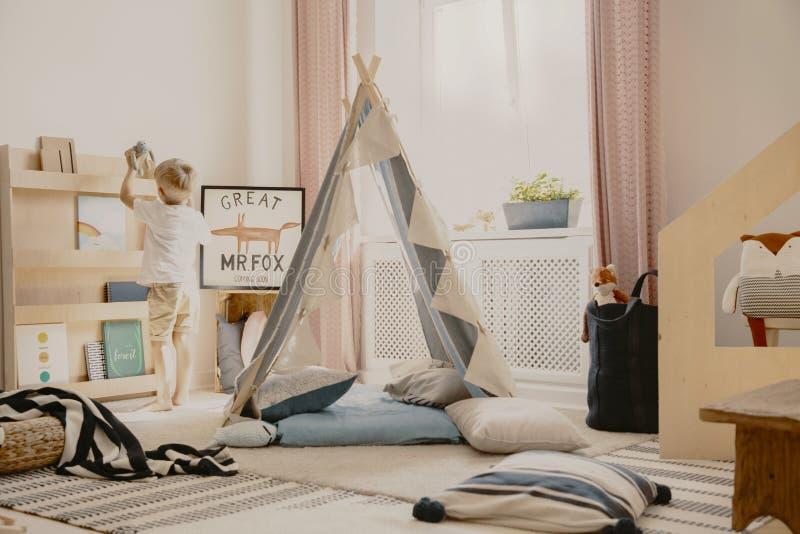 Hemtrevliga unges rum med pastellfärgade kulöra gardiner och det scandinavian tältet med kuddar, verkligt foto fotografering för bildbyråer