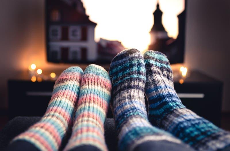 Hemtrevliga woolen sockor Koppla ihop hållande ögonen på tv i vinter Man och kvinna som använder online-strömmande service för fi royaltyfria bilder