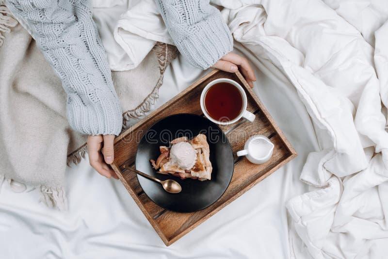 Hemtrevligt flatlay av säng med trämagasinet med pajen, glass och svart te och händer för kvinna` s arkivfoto