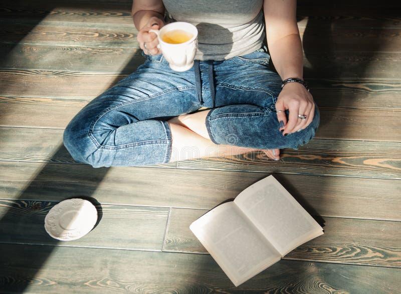 Hemtrevligt foto av den unga kvinnan med kopp tesammanträde på golvet royaltyfri foto