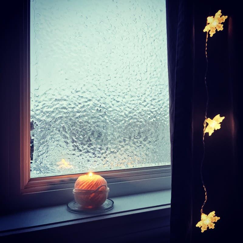 Hemtrevligt frostat fönster- och stearinljusljus fotografering för bildbyråer