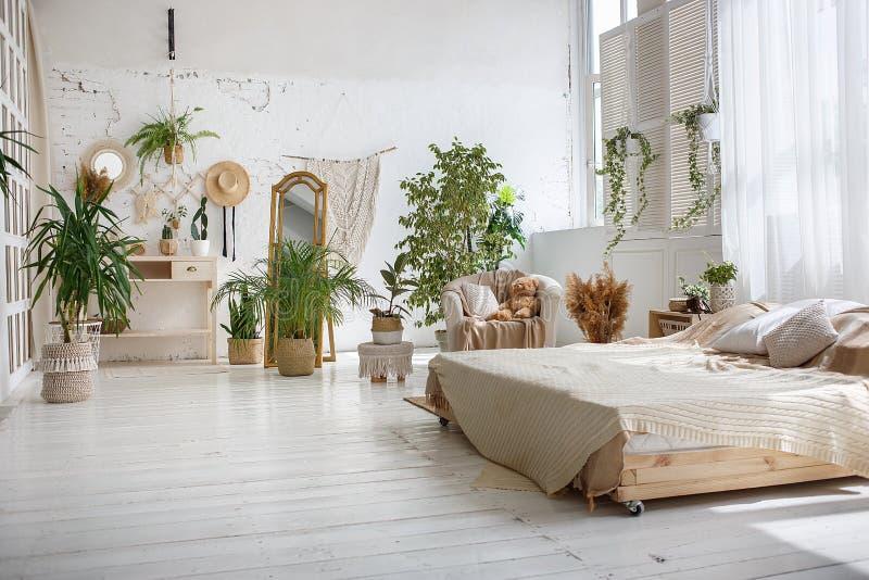 Hemtrevligt rum för stilfull ljus vind med dubbelsäng, fåtöljen, gröna växter, spegeln, vita tegelstenväggar och trägolvet royaltyfri foto