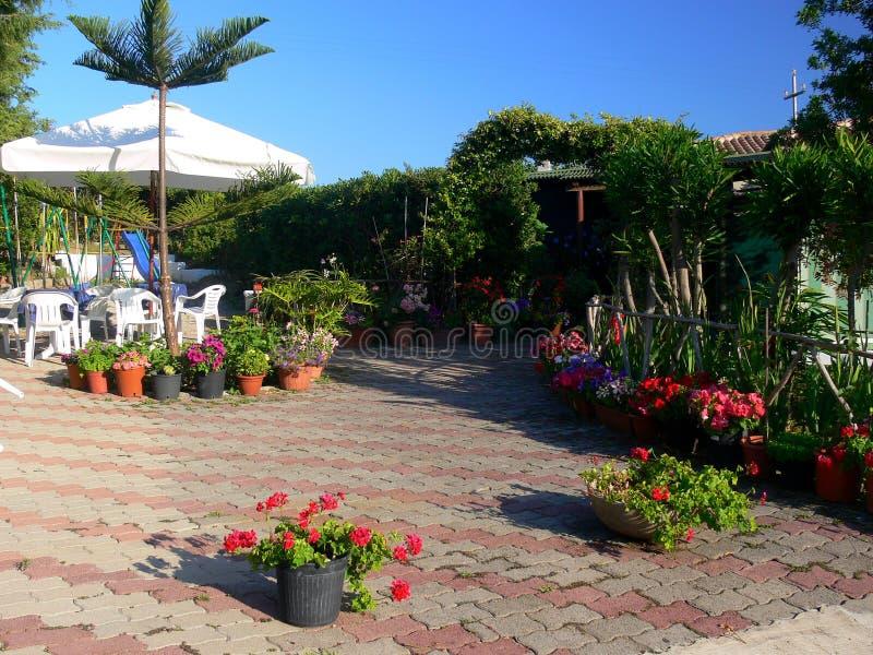 Hemtrevligt sammanträdeområde i trädgården med många blommor royaltyfri fotografi