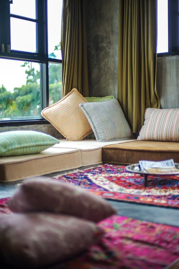 Hemtrevligt ställe med kuddar nära fönstren, ett bra ställe för läseböcker fotografering för bildbyråer