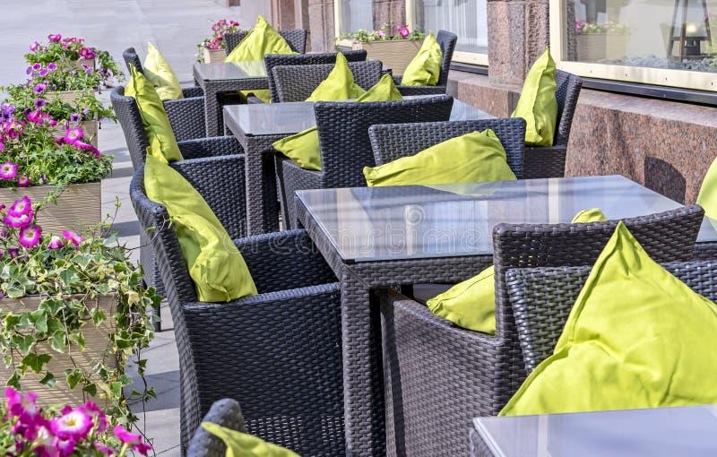 Hemtrevligt utomhus- kafé med vide- möblemang och gröna kuddar royaltyfria bilder