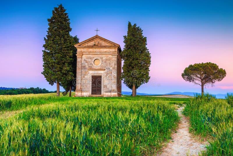 Hemtrevligt Vitaleta kapell och kornfält på solnedgången, Tuscany, Italien arkivbild