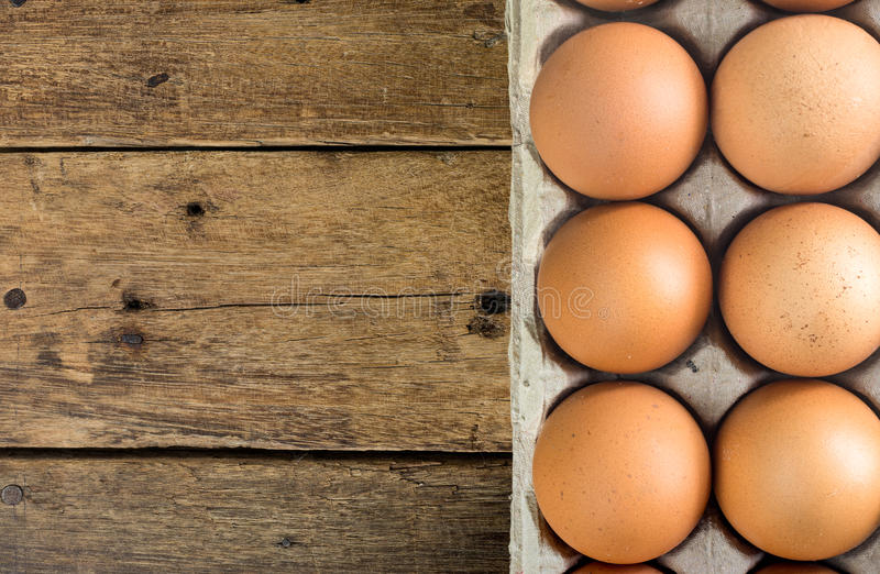 Hen eggs in brown pulp mold tray package on wooden table royalty free stock images