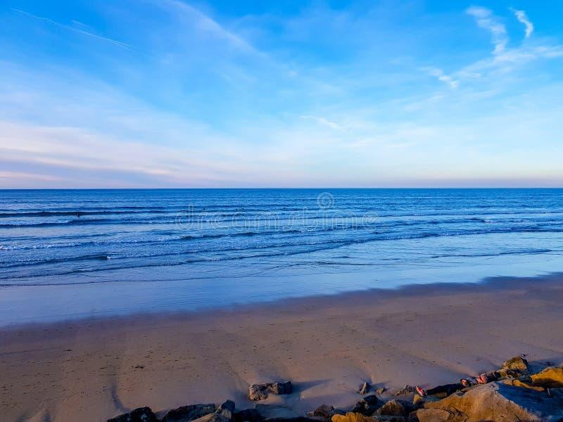 Hendaya海滩看法在日落的 当狗走在沙子和冲浪者在等待波浪的海 图库摄影