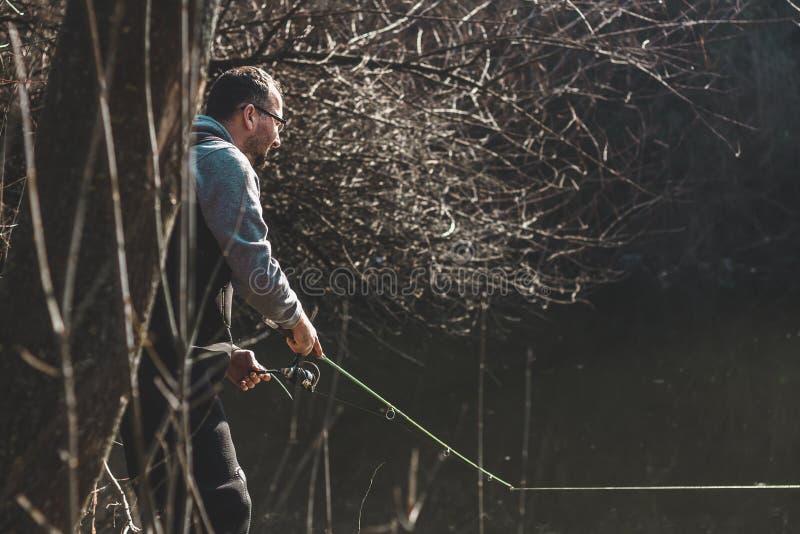 Hengel en handen van de visser over het meerwater stock afbeelding