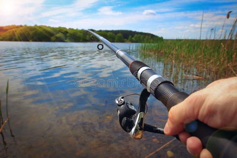 Hengel en handen van de visser over het meerwater royalty-vrije stock foto