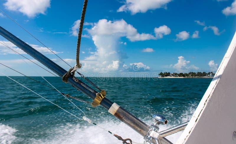 Hengels op diepzee vissersboot met mening van eiland in afstand onder blauwe hemel met pluizige witte wolken stock fotografie