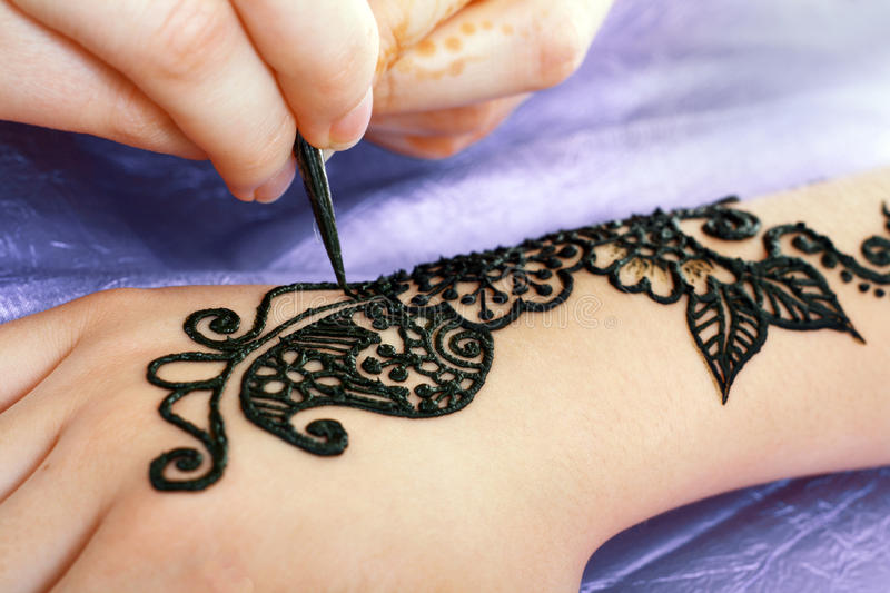 Henna being applied to hand royalty free stock images