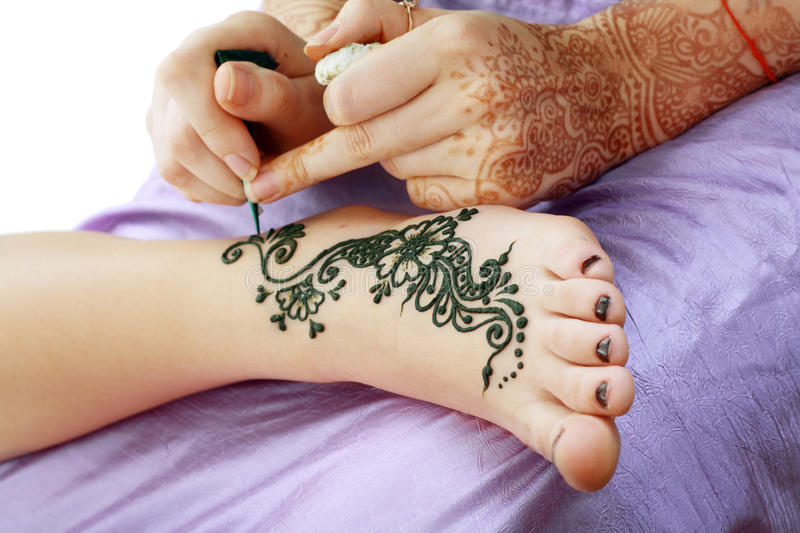 Henna being applied to leg royalty free stock image