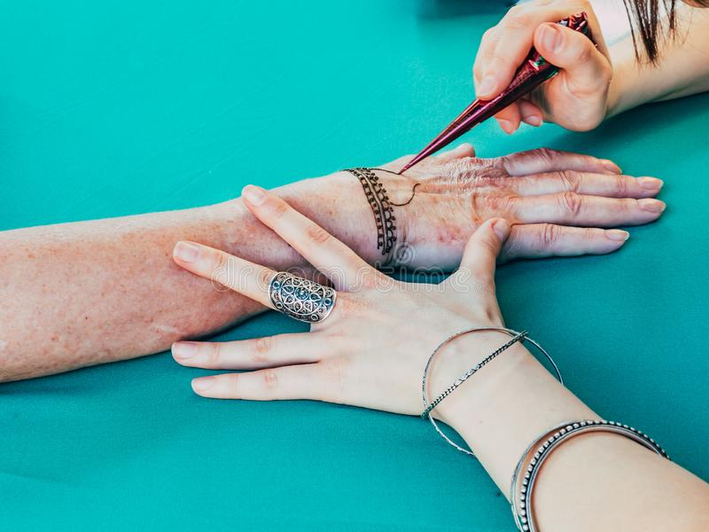 Henna painting female hand. Henna painting artist draws patterns on a hand. Arabian and Indian henna painting traditions stock image