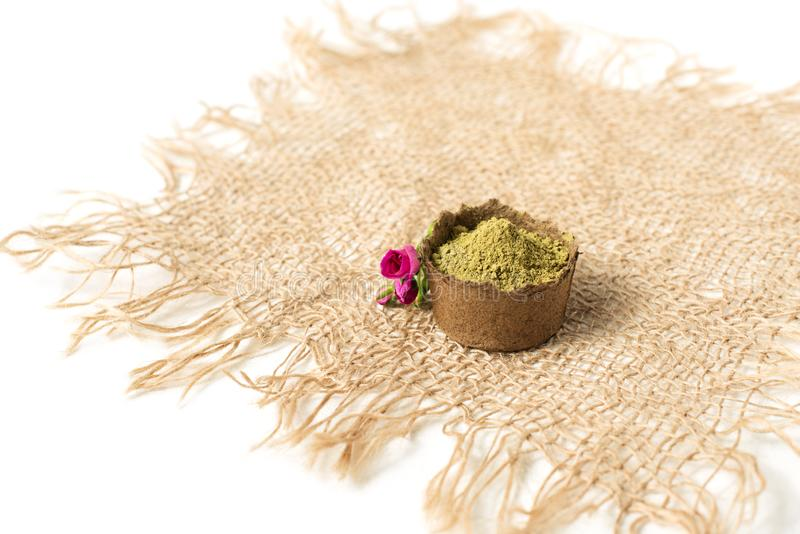 Henna powder for dyeing hair and eyebrows and drawing mehendi on hands,  with pink flower. stock photo