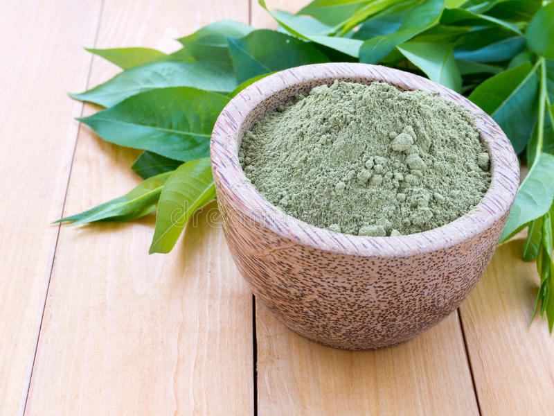 Henna safe hair dye powder. And green leaves on the wooden table stock photo