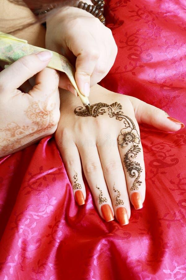 Henna som appliceras till handen arkivbild