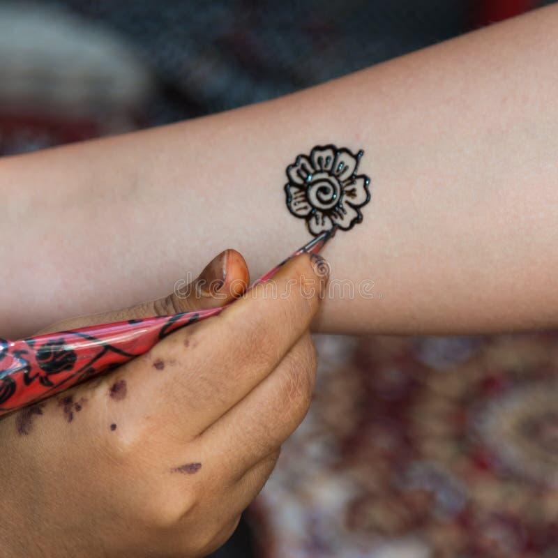 Henna Tatoo floral de tiragem no braço fêmea fotografia de stock royalty free