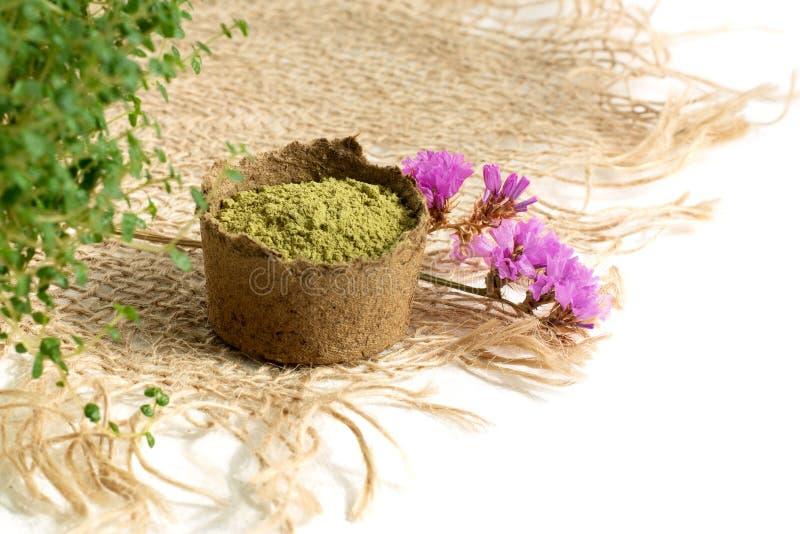 Hennastrauchpulver für färbendes Haar und Augenbrauen und Zeichnen mehendi auf Händen, mit grünen Blättern, rosa Blumen und  lizenzfreies stockfoto