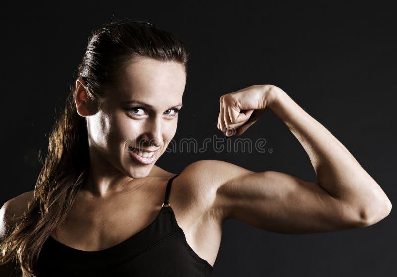 henne muskler som visar smileysportswomanen royaltyfria foton