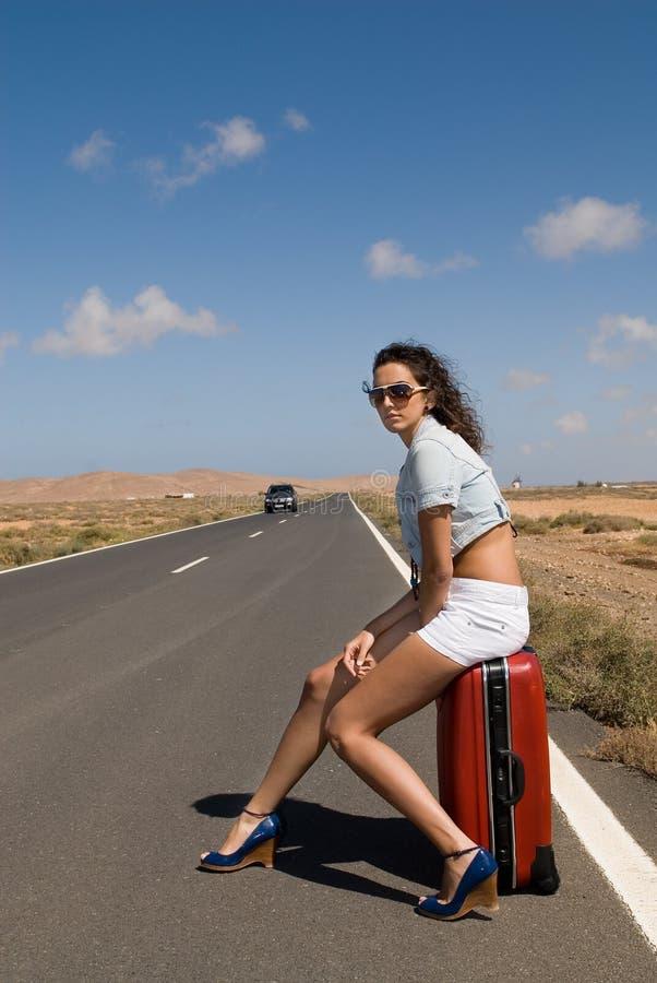 henne sittande resväskakvinna för väg arkivbild