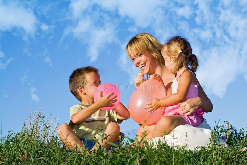 henne ungar som leker kvinnan royaltyfri foto