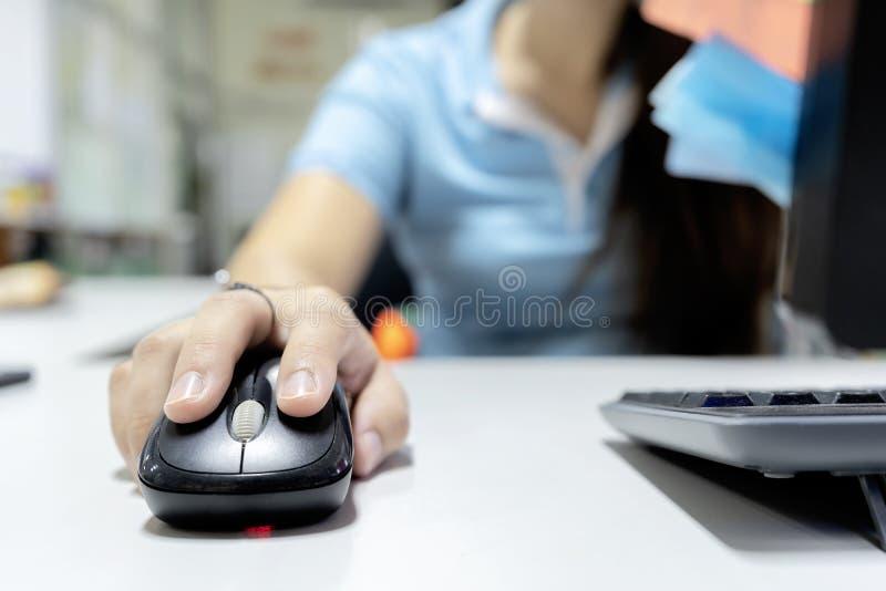 Hennes hand rymmer musen för att befalla datoren arkivbild